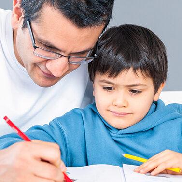 Dad and boy writing