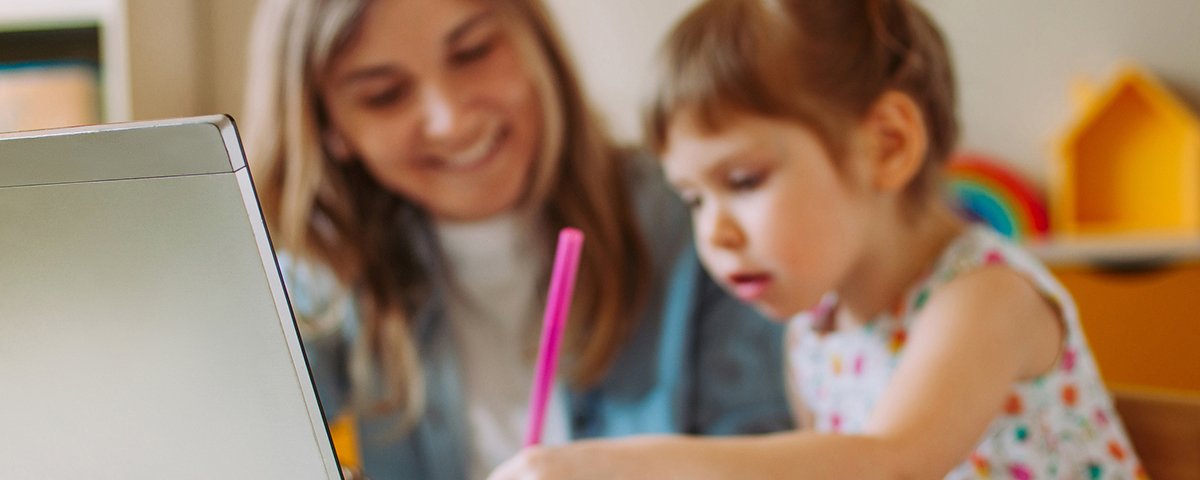 Mom and preschool daughter doing activity in front of computer